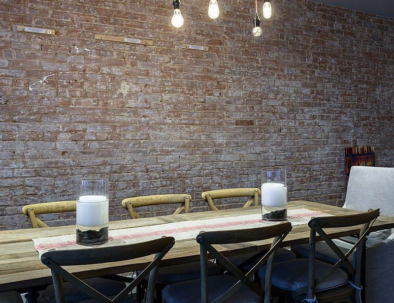 exposed-brick-wall-lighting-and-wooden-table-for-an-industrial-loft-inspired-dining-room